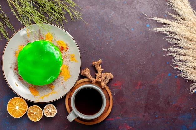 Vista de cima um pequeno bolo delicioso com uma xícara de chá na superfície roxa escura