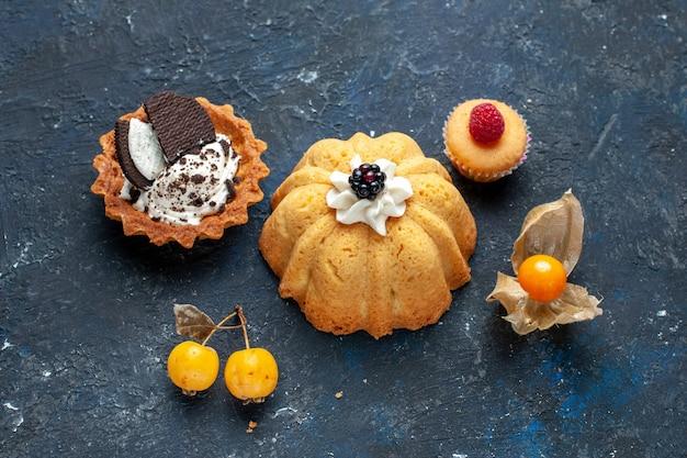 Vista de cima um pequeno bolo delicioso junto com um biscoito na mesa escura bolo de biscoitos doce de frutas