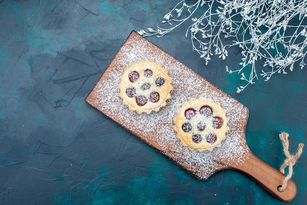 Vista de cima um pequeno bolo gostoso com açúcar em pó e cerejas no fundo azul escuro bolo de frutas doce cor da foto