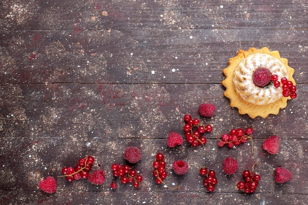 Vista de cima um pequeno bolo gostoso com açúcar em pó junto com framboesas e cranberries ao longo de fundo marrom rústico bolo de frutas vermelhas cor de biscoito
