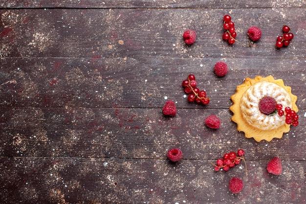 Vista de cima um pequeno bolo gostoso com açúcar em pó junto com framboesas e cranberries ao longo de um fundo marrom cor de biscoito de bolo de frutas vermelhas