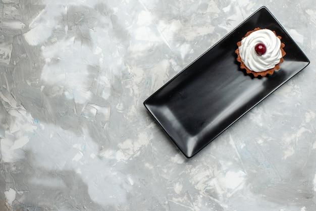 Vista de cima um pequeno bolo gostoso com creme dentro de um molde preto na mesa de luz bolo asse chá de açúcar doce