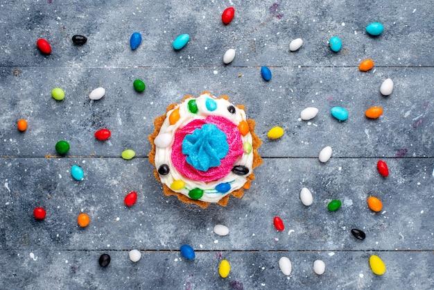 Vista de cima um pequeno bolo gostoso com creme e diferentes doces coloridos em toda a mesa clara.