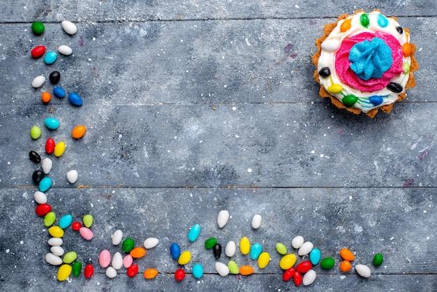 Vista de cima um pequeno bolo gostoso com creme e diferentes doces coloridos em toda a mesa de luz.