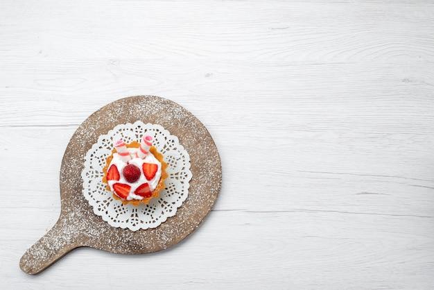 Vista de cima um pequeno bolo gostoso com creme e morangos fatiados no fundo branco bolo baga doce açucar