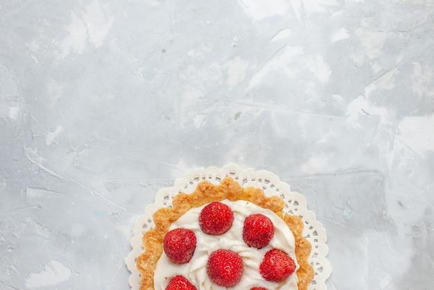 Vista de cima um pequeno bolo gostoso com creme e morangos vermelhos frescos no fundo branco-cinza