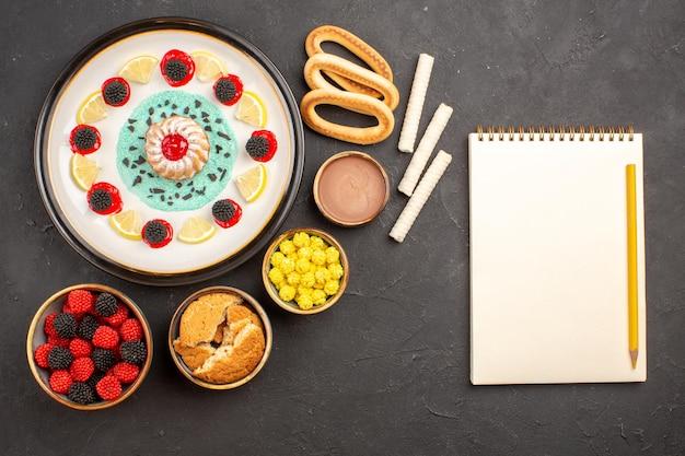 Vista de cima um pequeno bolo gostoso com doces e rodelas de limão em um fundo escuro.