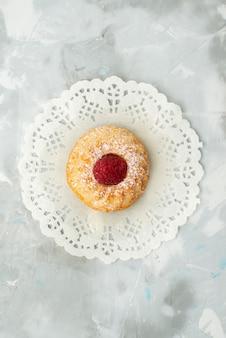 Vista de cima um pequeno bolo gostoso com framboesa na mesa leve de massa doce