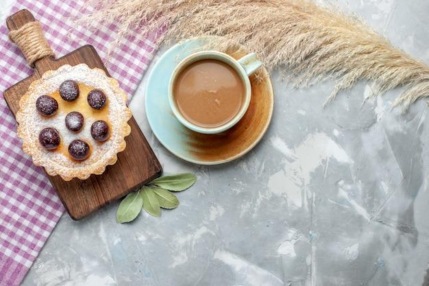 Vista de cima um pequeno bolo gostoso com frutas com açúcar em pó e café com leite em uma mesa de luz.
