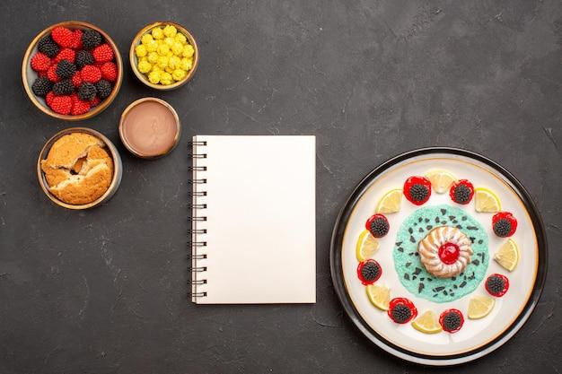 Vista de cima um pequeno bolo gostoso com rodelas de limão e confitures doces em fundo escuro.