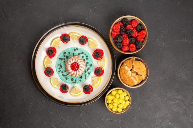 Vista de cima um pequeno bolo gostoso com rodelas de limão e doces em fundo escuro.