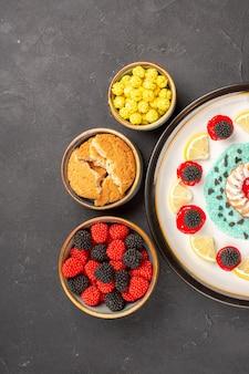Vista de cima um pequeno bolo gostoso com rodelas de limão e doces em um fundo escuro.