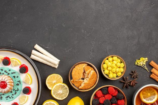 Vista de cima um pequeno bolo gostoso com rodelas de limão e uma xícara de chá no fundo escuro.