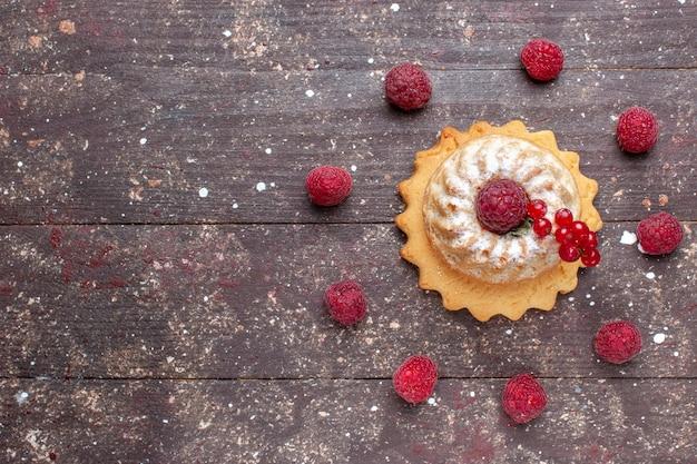 Vista de cima um pequeno bolo simples com açúcar em pó, framboesa e cranberries no fundo marrom.