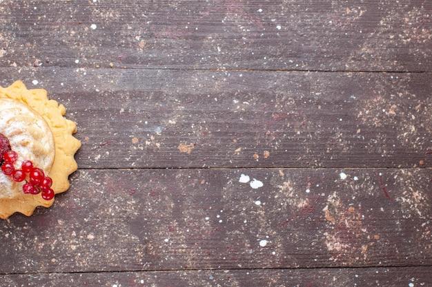 Vista de cima um pequeno bolo simples com açúcar em pó, framboesa e cranberries no fundo rústico de madeira marrom