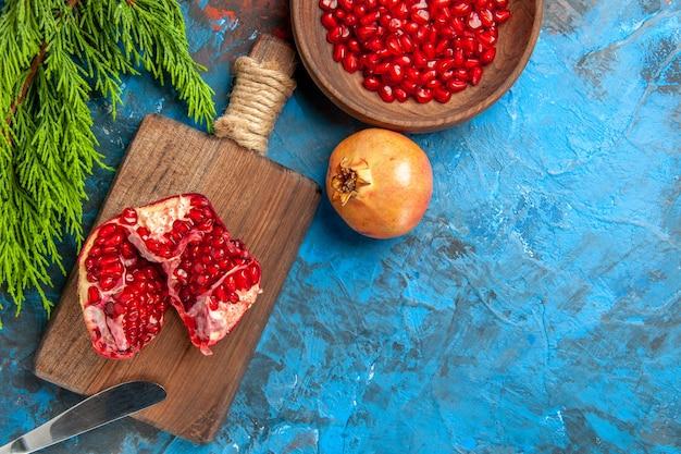 Vista de cima uma faca de romã cortada na tábua de cortar sementes de romã em uma tigela e romãs no fundo azul