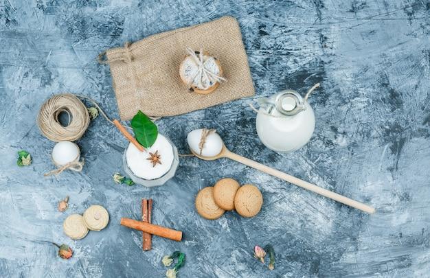 Vista de cima uma jarra de leite e uma tigela de vidro de iogurte com colheres, biscoitos, ovos, clew, canela e uma planta na superfície de mármore azul escuro. horizontal