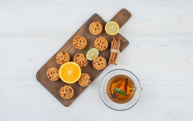 Vista de cima uma laranja, limão, biscoitos e canela em uma tábua com uma xícara de chá na superfície branca