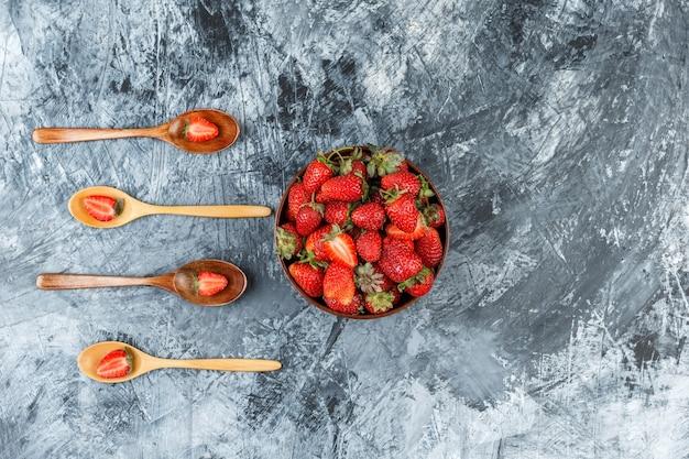 Vista de cima uma tigela de morangos com quatro colheres de pau na superfície de mármore azul escuro. horizontal