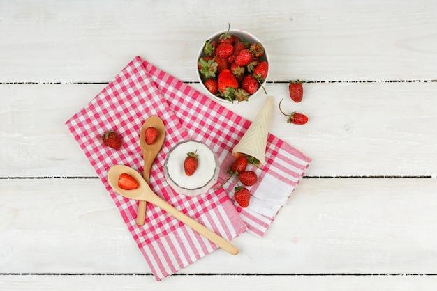 Vista de cima uma tigela de morangos na toalha vermelha guingão com colheres de pau, um cone de morangos e uma tigela de iogurte na superfície da placa de madeira branca. horizontal