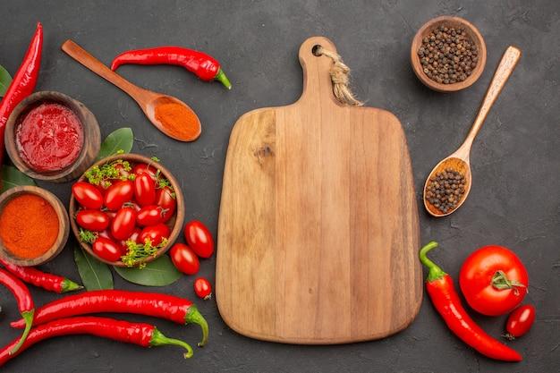 Vista de cima uma tigela de tomate cereja pimenta vermelha picante pimenta preta em uma colher de pau tigelas de ketchup e pimenta preta e uma tábua de cortar no fundo preto