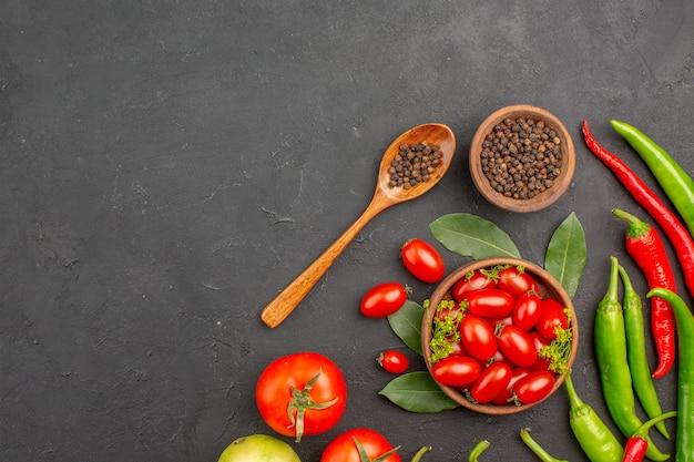Vista de cima uma tigela de tomate cereja pimenta vermelha picante pimenta preta em uma colher de pau uma tigela de pimenta preta no fundo preto