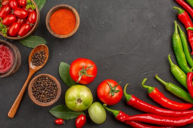 Vista de cima uma tigela de tomates cereja quentes pimentões vermelhos e verdes e folhas de louro de tomates tigelas de ketchup pimenta vermelha em pó e pimenta preta e uma colher em solo preto