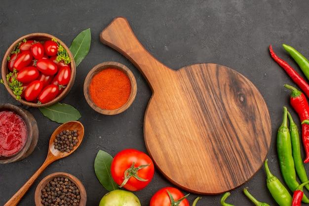 Vista de cima uma tigela de tomates cereja quentes pimentões vermelhos e verdes e folhas de louro de tomates tigelas de ketchup pimenta vermelha em pó e pimenta preta e uma tábua de cortar no chão