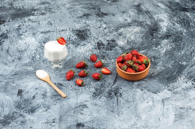 Vista de cima uma tigela de vidro de iogurte em uma toalha de mesa de vime com uma colher de pau e morangos no mármore azul escuro e a superfície da placa de madeira branca. vertical