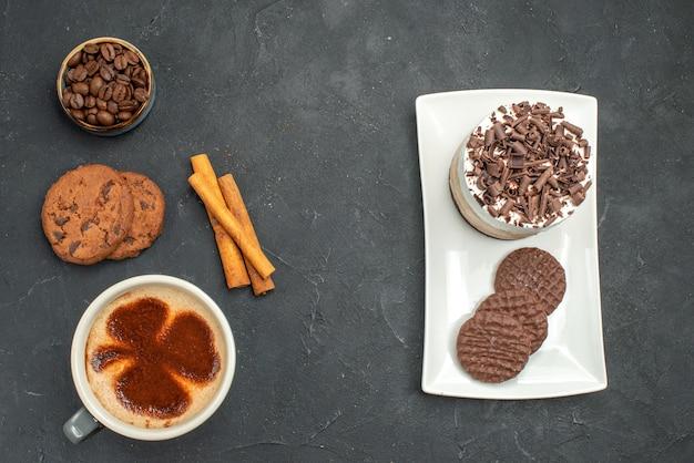 Vista de cima uma xícara de bolo de café e biscoitos em um prato branco sobre fundo escuro isolado