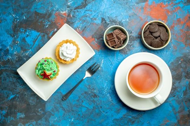 Vista de cima uma xícara de bolos de chá em um prato de chocolates em pequenas tigelas na superfície vermelha azul