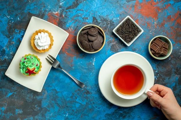 Vista de cima, uma xícara de chá, bolos pequenos de chocolate na superfície azul vermelha
