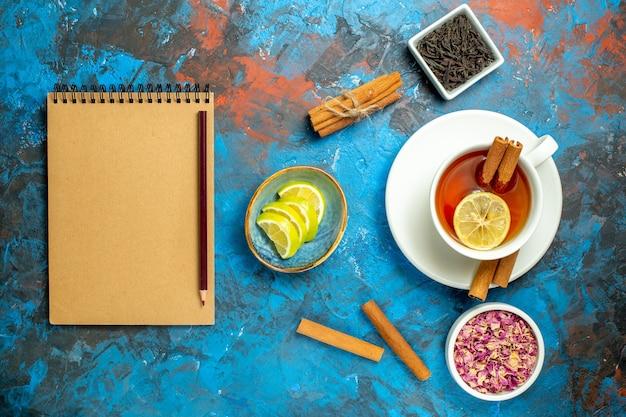 Vista de cima, uma xícara de chá, canela, fatias de limão, lápis, caderno, azul, vermelho