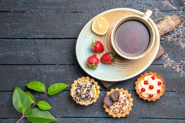 Vista de cima uma xícara de chá com fatia de limão e morangos em folhas de tortas de pires na mesa de madeira escura