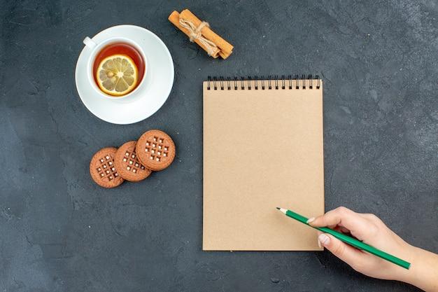 Vista de cima, uma xícara de chá com limão, paus de canela, biscoitos, bloco de notas, lápis verde, mão feminina, superfície escura
