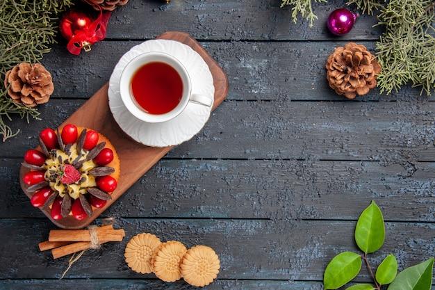 Vista de cima uma xícara de chá e bolo de frutas vermelhas em um prato de servir de madeira, pinhas de canela, brinquedos de natal, biscoitos e folhas na mesa de madeira escura