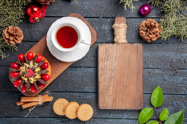 Vista de cima uma xícara de chá e bolo de frutas vermelhas na placa de serviço de madeira, folhas de brinquedos de natal de pinhas e uma tábua de cortar na mesa de madeira escura