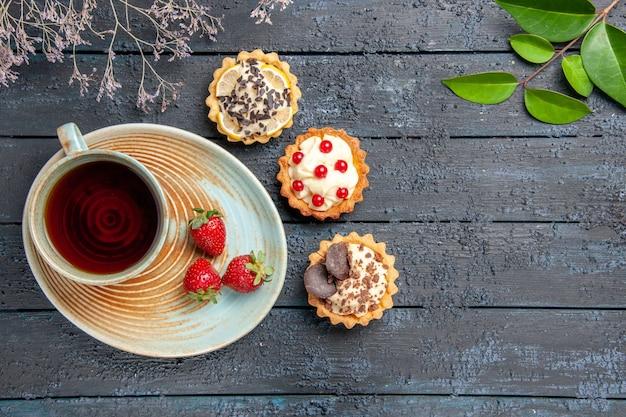 Vista de cima uma xícara de chá e morangos em folhas de tortas de pires e galho de flor seca na mesa de madeira escura