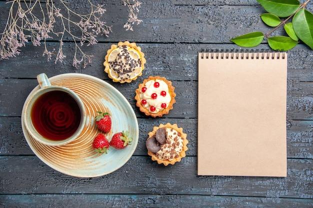 Vista de cima uma xícara de chá e morangos em folhas de tortas de pires e um caderno na mesa de madeira escura