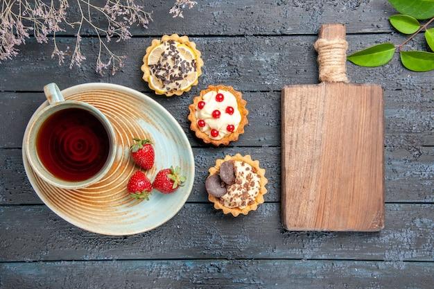 Vista de cima uma xícara de chá e morangos em folhas de tortas de pires e uma tábua de cortar na mesa de madeira escura