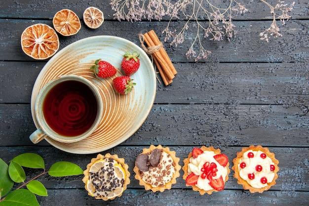 Vista de cima, uma xícara de chá e morangos em pires, tortas de laranjas secas com canela e folhas em fundo escuro
