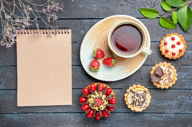 Vista de cima, uma xícara de chá e morangos em pires, tortas de laranjas secas, folhas de bolo de frutas vermelhas e um caderno na mesa de madeira escura