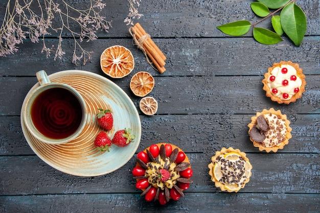 Vista de cima, uma xícara de chá e morangos em pires, tortas de laranjas secas, folhas de canela e bolo de frutas vermelhas na mesa de madeira escura