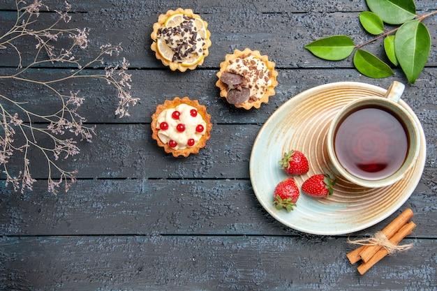 Vista de cima uma xícara de chá e morangos em tortas de pires e folhas de canela na mesa de madeira escura