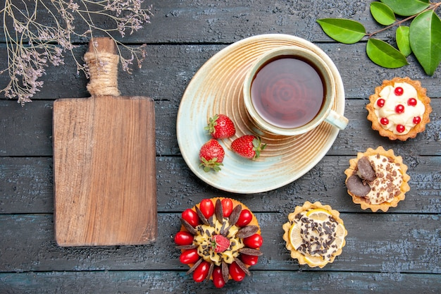 Vista de cima, uma xícara de chá e morangos em um pires, tortas de laranjas secas, folhas de bolo de frutas silvestres e uma tábua de cortar na mesa de madeira escura