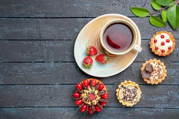 Vista de cima uma xícara de chá e morangos no pires, folhas secas de tortas de laranja e bolo de frutas vermelhas à direita da mesa de madeira escura