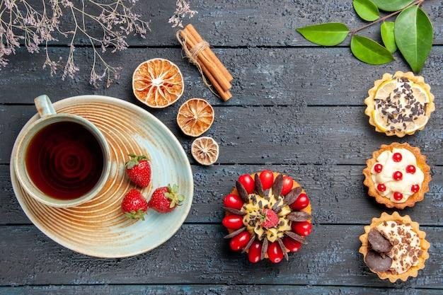 Vista de cima, uma xícara de chá e morangos no pires, folhas secas de tortas de laranja e bolo de frutas vermelhas na mesa de madeira escura