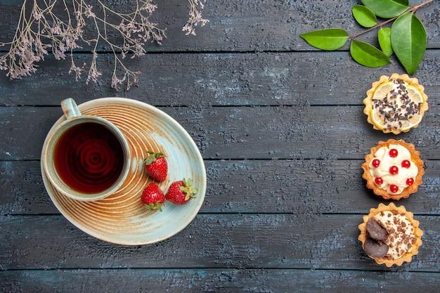 Vista de cima uma xícara de chá e morangos no pires no lado esquerdo, folhas de tortas no lado direito da mesa de madeira escura