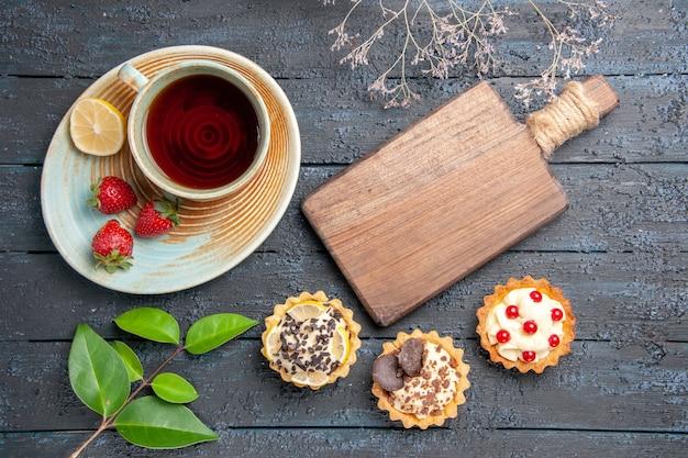 Vista de cima uma xícara de chá, fatia de limão e morangos em folhas de tortas de pires e uma tábua de cortar na mesa de madeira escura