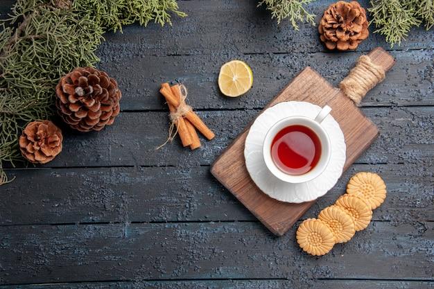 Vista de cima, uma xícara de chá na tábua de cortar uma fatia de biscoitos de pinha de limão e canela no fundo escuro de madeira